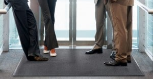 employees standing on a black entrance mat