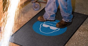 employee standing on a safety message mat