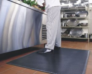 kitchen staff standing on a black anti-fatigue mat