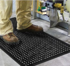male employee standing on a black wet area mats