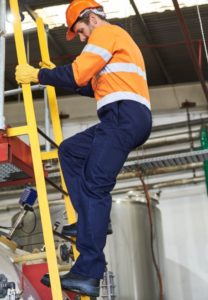 male industrial worker climbing down the yellow ladder