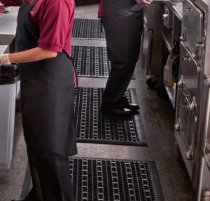 kitchen staff standing on a black wet area mats