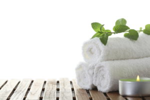 three clean white cotton towels with candles and leaves