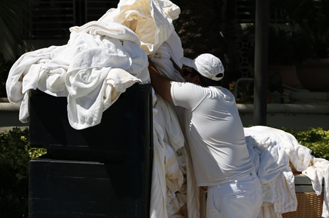Person collecting the white linens for laundry