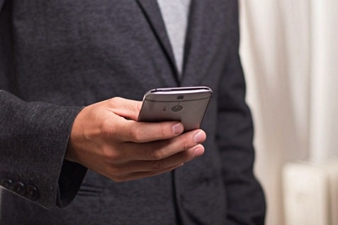 Male employee holding a mobile phone