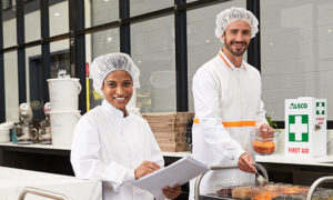 male and female food processing employees wearing clean uniforms