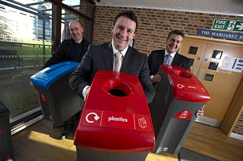 Three male employees holding recycle bins