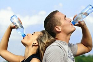 Female and male drinking a bottled water.