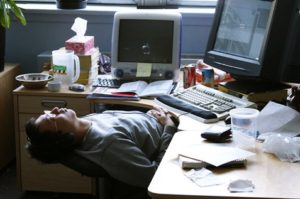 Male employee lying down and listening to music while at work