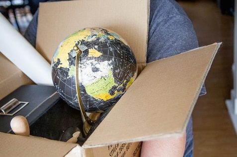 An individual carrying a cardboard box with a globe and other items inside