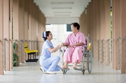 A nurse assisting an old woman