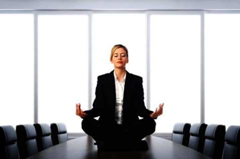 Female employee meditating on top of the table