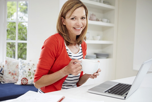 Happy woman drinking coffee while working at home