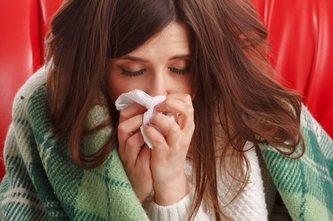 A sick woman blowing her nose using a tissue