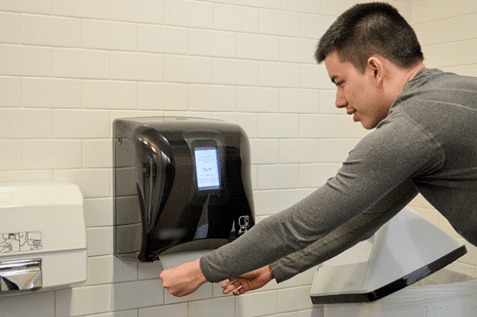 Man pulling a paper towel from a dispenser