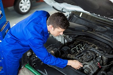 Mechanic servicing automobile car engine in repair garage