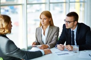Male and female executives talking to a male candidate.