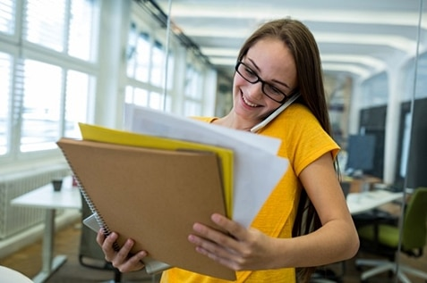 Female employee smiling while looking at her paperworks.