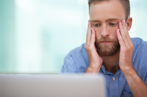 Man working at laptop in stress
