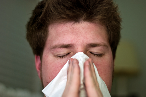 A cold man sneezes in a tissue.